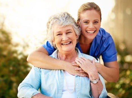 A caregiver wrapping her arms around an Elderly woman posing for a photo while smiling outside