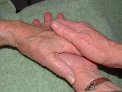 Elderly hands holding one another