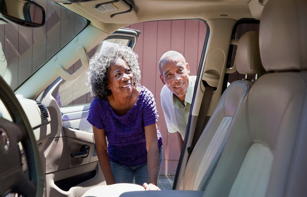 Senior couple looking inside their car
